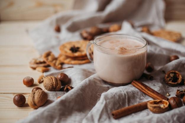 Cacao chaud avec des biscuits, des bâtons de cannelle, de l'anis, des noix sur une table en bois. vue de face, espace copie.