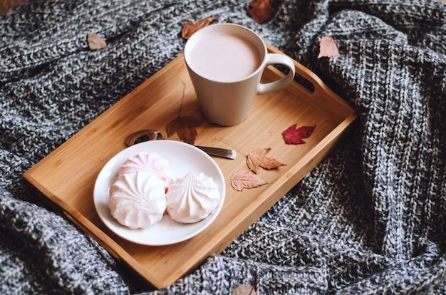 Cacao chaud avec des bonbons sur un plateau en bois sur un plaid en laine tricoté chaud avec des feuilles.