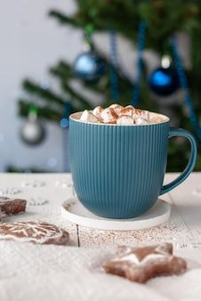 Cacao chaud dans une tasse turquoise avec des guimauves et des biscuits en pain d'épice sur un tableau blanc