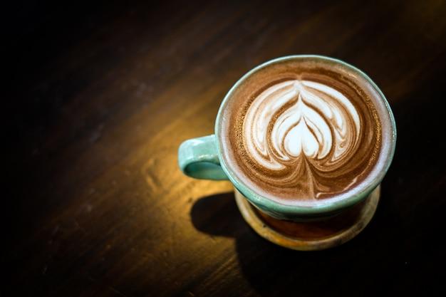Cacao frais chaud fait maison avec de la mousse de lait blanche à motifs sur la surface dans une tasse.