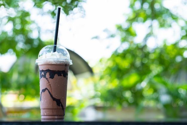 Cacao froid dans des verres en plastique avec le bokeh en toile de fond de feuilles vertes.