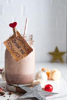 Cacao à la guimauve et des pailles dans le bocal en verre avec une pancarte «bois moi décoré»