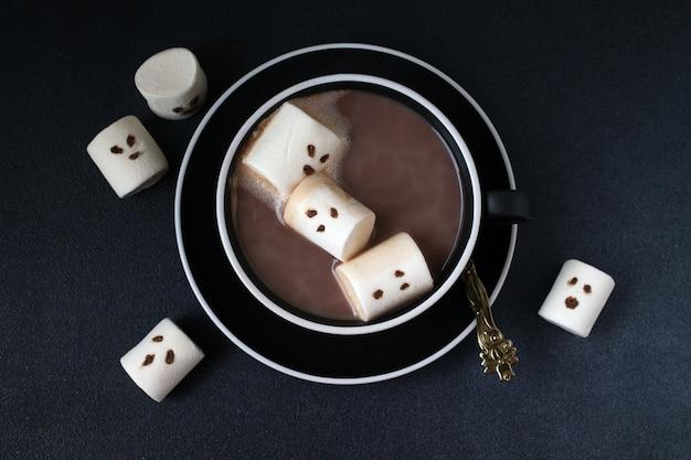 Cacao d'halloween et guimauves avec des grimaces sur fond noir