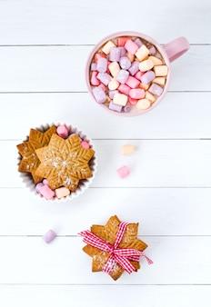 Cacao de noël avec guimauve dans une tasse rose et un biscuit au gingembre sur une table en bois