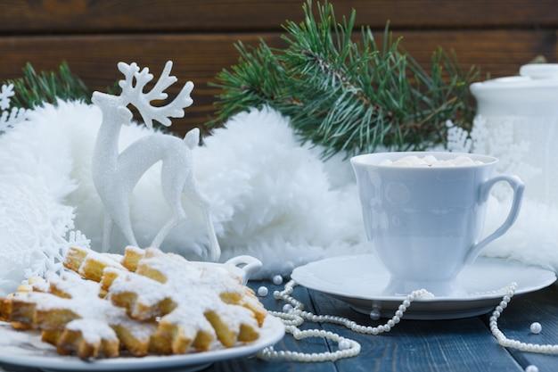 Cacao de noël avec des guimauves et des cookies sur fond de bois