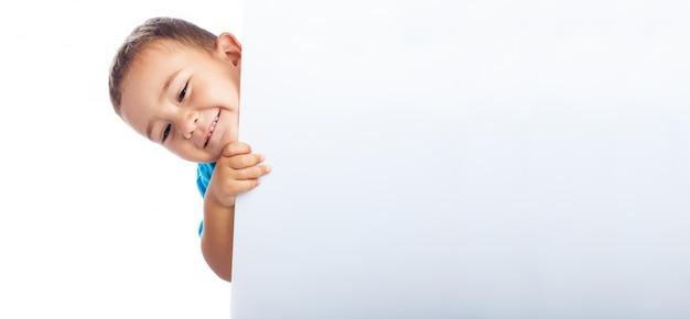 Cachant enfant derrière une affiche blanche