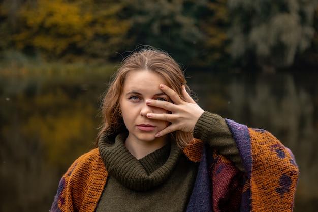 Cache-cache. la fille a couvert son visage avec ses mains. portrait de gros plan sur un lac le concept de la douleur féminine, la tristesse, la violence, la dépression, la solitude.