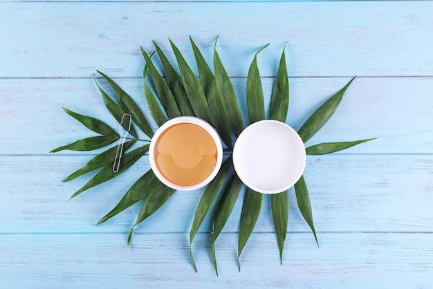 Cache-œil cosmétique doré hydrogel en pack sur un fond en bois avec des feuilles de palmier.