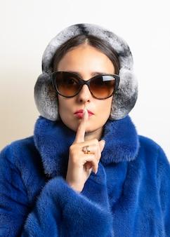 Cache-oreilles en fourrure d'hiver sur femme en manteau de fourrure bleu.