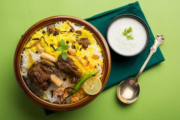 Cachemire mutton gosht ou lamb biryani préparé dans du riz basmati servi avec trempette au yaourt sur fond de mauvaise humeur, mise au point sélective