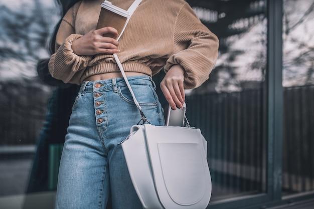Cacher un smartphone. gros plan photo d'une femme mettant son smartphone dans son sac