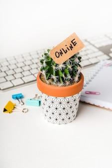 Un cactus portant l'étiquette «en ligne» se dresse sur un bureau avec un clavier