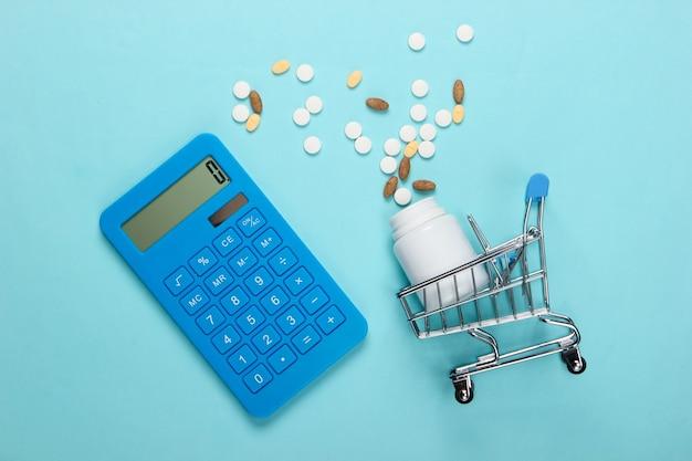 Caddie avec bouteille de pilules, calculatrice sur bleu