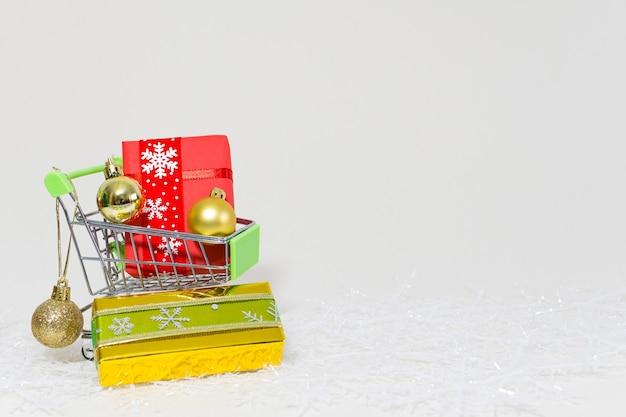 Caddie avec coffrets cadeaux et sphères dorées sur un flocon de neige sur fond blanc