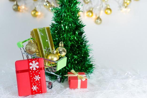 Caddie avec coffrets cadeaux et sphères dorées sur des flocons de neige sur fond blanc