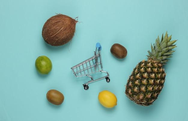 Caddie et fruits tropicaux sur fond bleu. faire du shopping au supermarché. concept de nourriture saine. vue de dessus