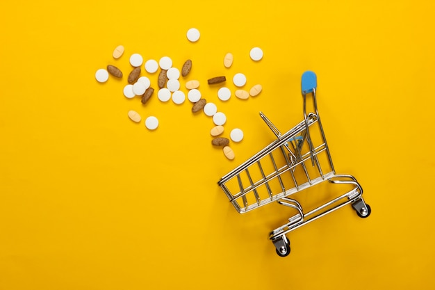 Caddie avec des pilules sur jaune