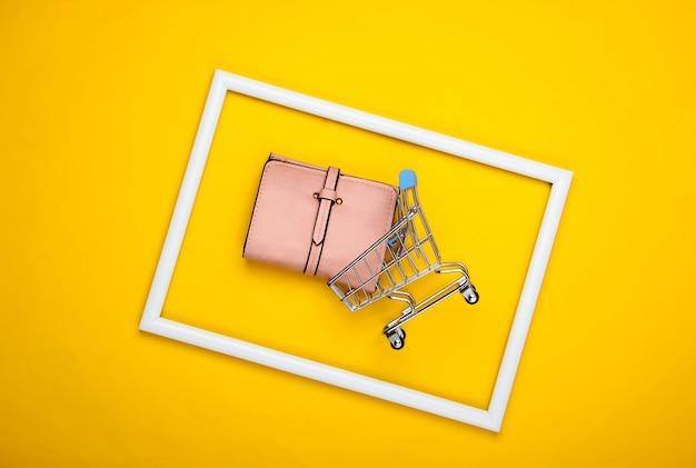 Caddie avec portefeuille en cuir dans un cadre blanc sur surface jaune