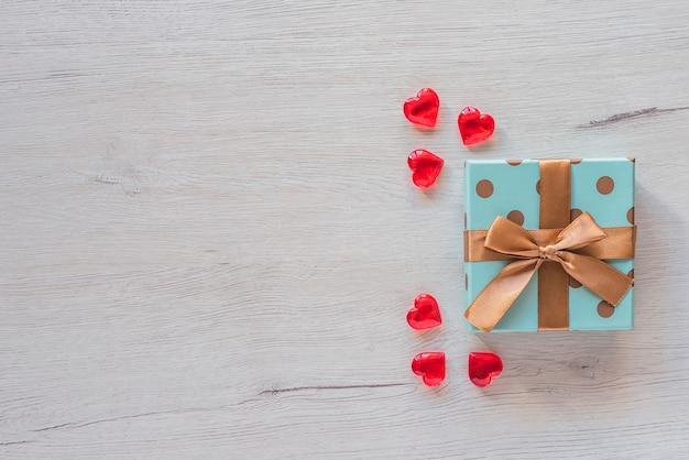 Cadeau avec archet sur table en bois, avec des coeurs rouges