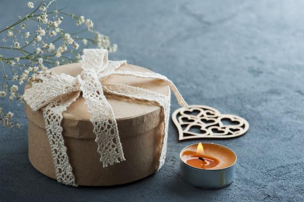 Cadeau artisanal avec noeud, bougie allumée
