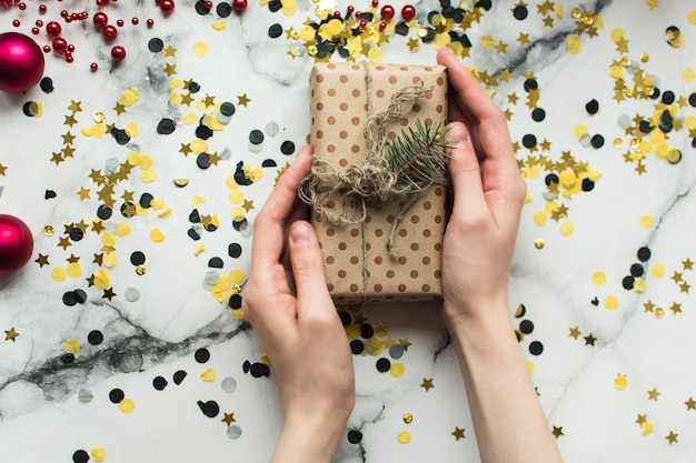 Cadeau d'artisanat avec un arc de ficelle et un brin d'arbre de noël entouré de confettis