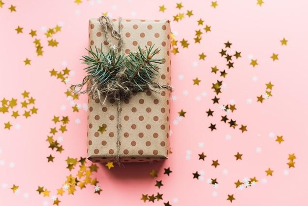 Cadeau d'artisanat avec ficelle et branche de pin sur pastel rose avec des confettis d'or.