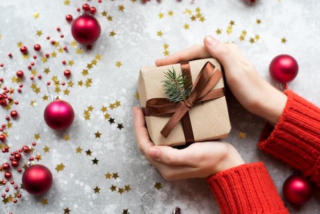 Cadeau d'artisanat en papier brun avec des brindilles de sapin de noël et de la ficelle entre les mains d'une fille avec un pull rouge et une manucure nude.