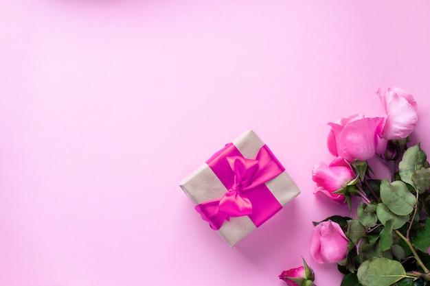 Cadeau attaché avec un ruban rose et un bouquet de roses roses. saint valentin, noël, fête des mères, cadeaux d'anniversaire. concept de carte de voeux