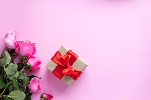 Cadeau attaché avec ruban rouge et bouquet de roses roses. saint valentin, noël, fête des mères, cadeaux d'anniversaire. concept de carte de voeux