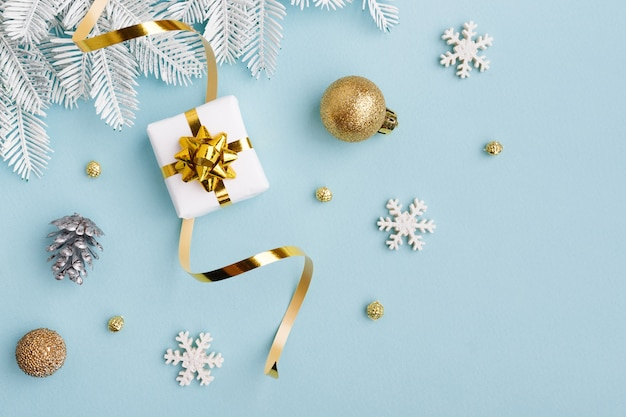 Cadeau blanc avec noeud en or et décorations de noël sur papier bleu pastel