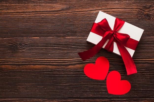Cadeau blanc avec un ruban rouge et des coeurs en papier isolés sur un fond en bois foncé. vue de dessus d'un flatlay chaud célébrant. concept de la saint-valentin et de noël. copyspace.
