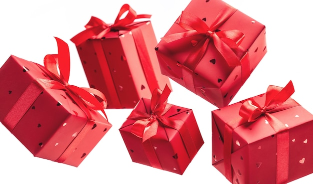 Cadeau en boîte emballé dans un élégant papier rouge avec noeud