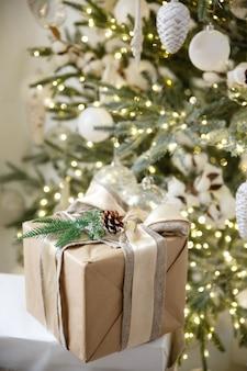 Cadeau en boîte sur fond de guirlande de noël brûlant et arbre du nouvel an