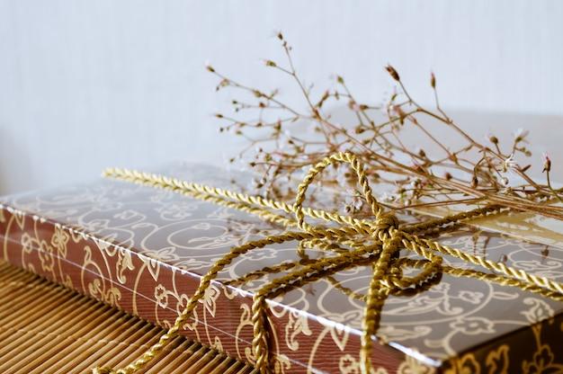 Cadeau en boîte et petit bouquet de fleurs. fête d'anniversaire.