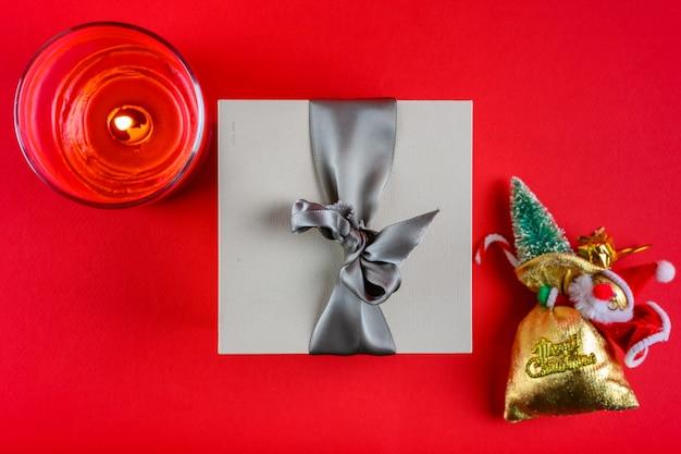 Un cadeau, une bougie du père noël sur fond rouge. décoration de noël.