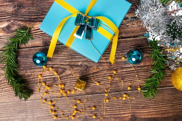 Un cadeau avec des boules bleues emballées avec un emballage bleu et de petits cadeaux en or situés sur une table en bois et sur un fond blanc. fond de bois. l'atmosphère de magie.