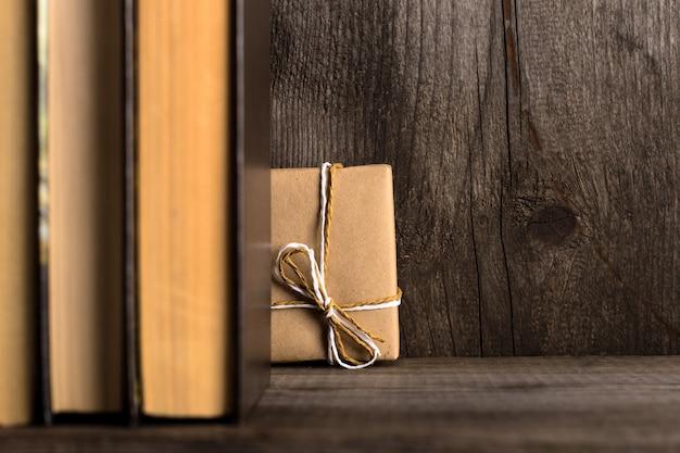 Un cadeau caché sur une étagère en bois derrière les livres.