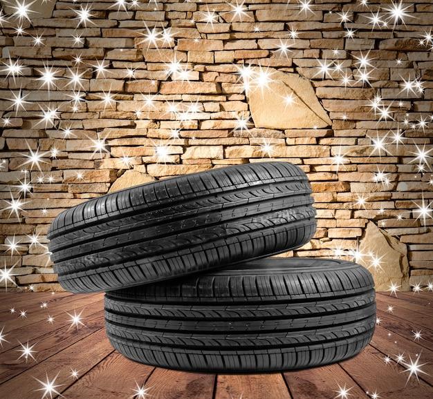Cadeau en caoutchouc de roue pour noël sur les arrière-plans texturés en bois dans un intérieur de pièce