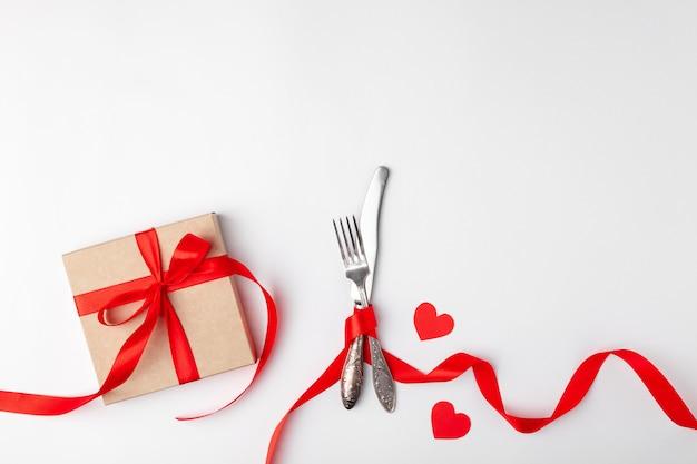 Cadeau et couverts attachés avec un ruban rouge