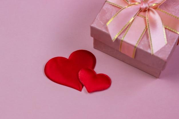 Un cadeau dans une belle boîte et des coeurs rouges sur fond rose.