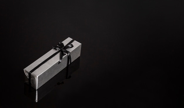 Cadeau dans un emballage en argent avec un ruban noir