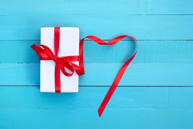 Cadeau dans un emballage blanc avec un ruban rouge