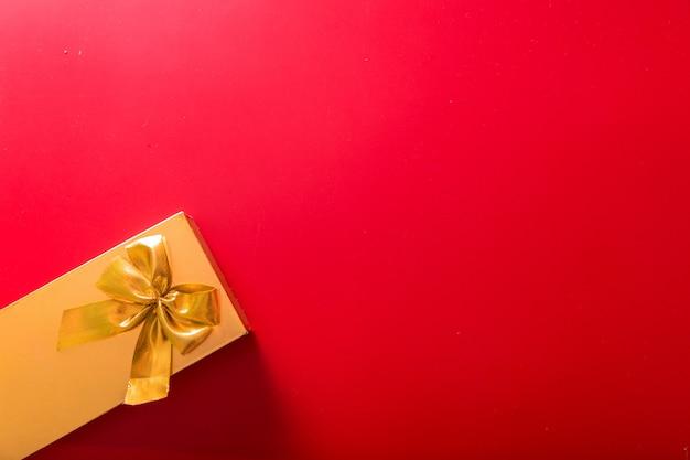 Cadeau dans un emballage doré avec un arc