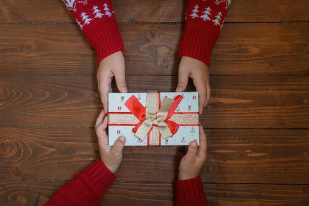 Cadeau dans les mains de deux enfants sur fond en bois foncé.
