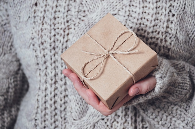 Cadeau dans les mains des femmes, gros plan. concept de cadeau monochrome et minimaliste. une fille en pull tient une boîte-cadeau en papier kraft, attachée avec une ficelle. fond de surprise.