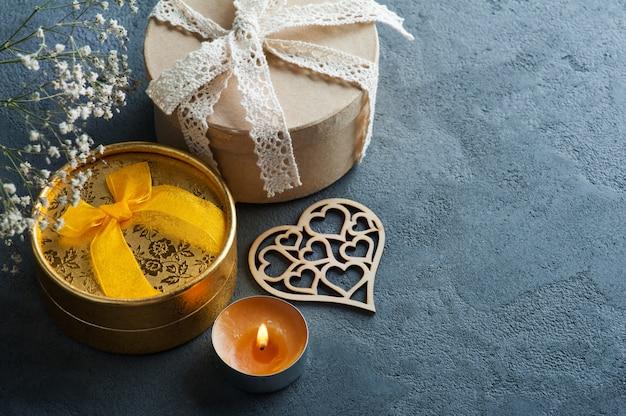 Cadeau doré fabriqué à la main avec un arc, une bougie allumée