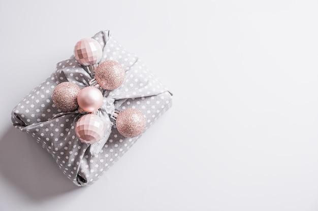 Cadeau durable de noël décoré de boules rose argenté pastel sur table grise
