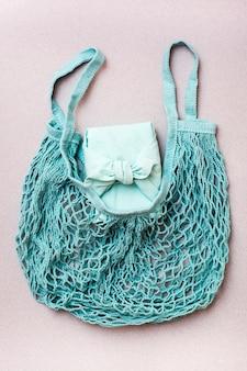 Cadeau écologique - boîte enveloppée de tissu dans un sac en filet sur fond gris. minimalisme. palette bleue
