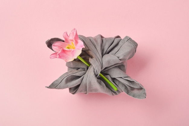 Cadeau écologique printanier emballé dans du textile gris avec une fleur de tulipe rose
