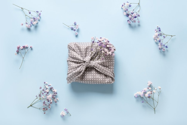 Cadeau écologique de printemps enveloppé de textile gris avec des fleurs sur fond bleu.